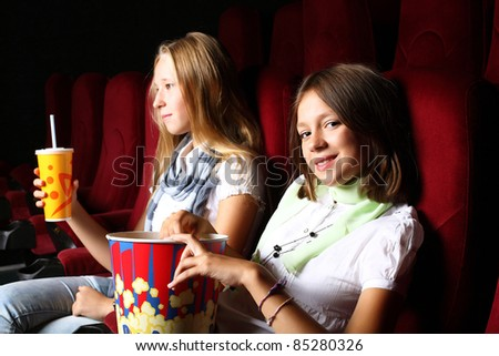 Two young girls watching movie in cinema