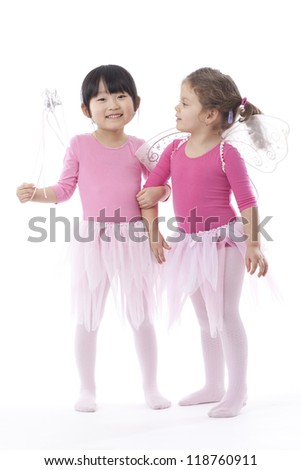 Two young girls wearing pink tutus shot in the studio against a white background. - stock photo