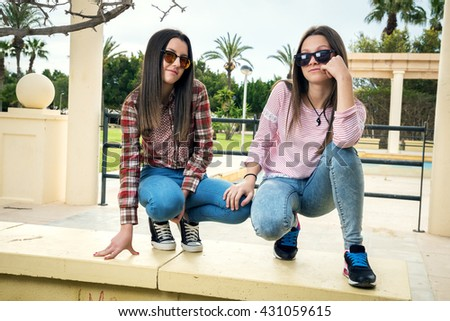 two young girls were photographed in park in sunglasses