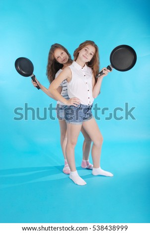 Two young girls with a frying pan isolated on blue background