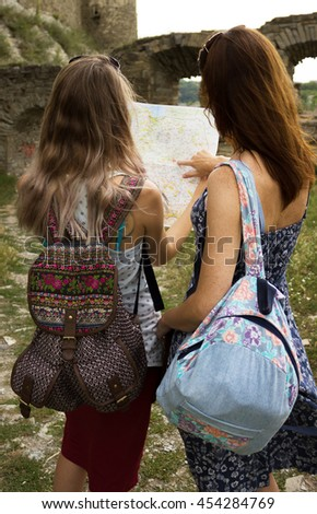 Two young girls with backpacks holding a city map, looking for the route. Women in the old historic town, many ruins. - stock photo
