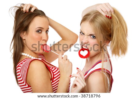Two young girls with lollipops having fun, on white background