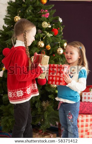 Two Young Girls With Presents In Front Of Christmas Tree - stock photo