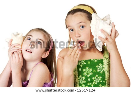 Two young gradeschool girls listening to seashell stories and secrets - stock photo