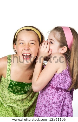 Two young gradeschool girls telling secrets and laughing - stock photo