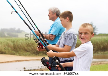two young grandsons fishing with their grandpa by the lake - stock photo