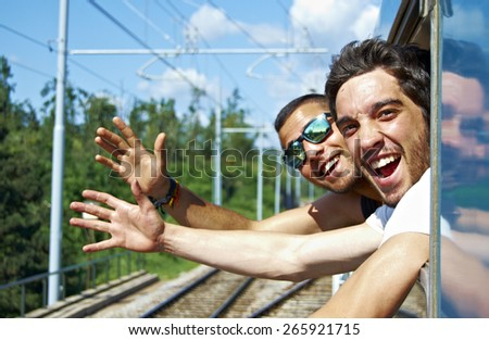 Two young greet and smiling through the window of a train - stock photo