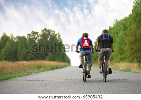 Two young guys on bicycles riding together on an asphalt road - stock photo