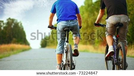 Two young guys riding on a bicycles on an empty asphalt road - stock photo