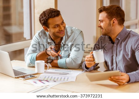 Two young handsome businessmen in casual clothes smiling, talking, drinking coffee, using laptop and tablet while working in office - stock photo