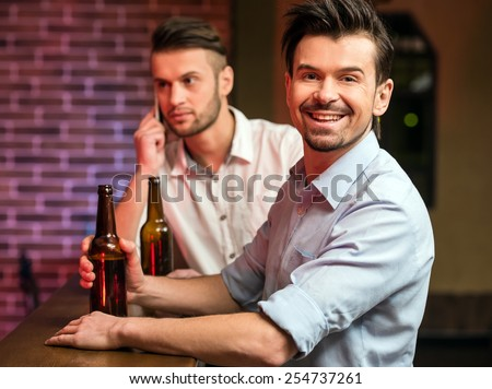 Two young handsome friends in a pub with bottle of beer are spending time together.