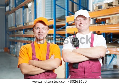 two young handsome workers man in uniform in front of warehouse rack arrangement stillages - stock photo