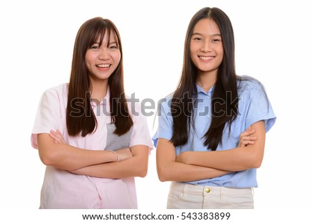 Two young happy Asian teenage girls smiling with arms crossed