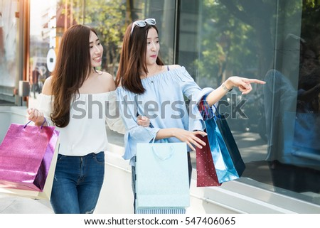 two young happy asian women shopping outdoor shopping mall in a holiday, vintage tone.