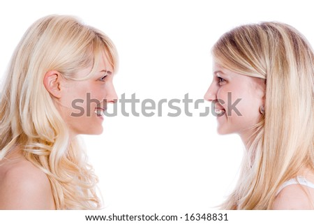 two young happy  girlfriends, profile, studio on white - stock photo