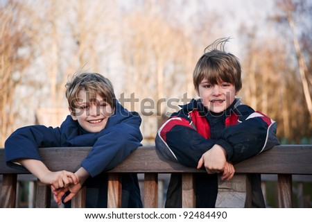 Two young happy handsome brothers playing outdoors in Autumn Fall - stock photo
