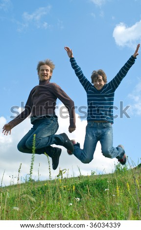 Two young happy men jumping against summer landscape