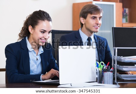 Two young happy russian managers using laptop at work in office