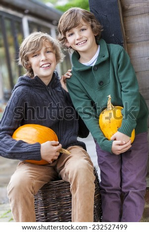 Two young happy smiling boys brothers outside with pumpkins - stock photo