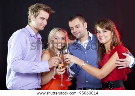 Two young happy smiling couples with champagne glasses at celebration, party or romantic date in night club - stock photo