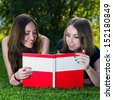 Two young happy smiling girls reading an open book in a summer green park - stock photo