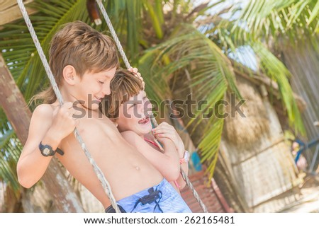 two young happy smiling kids - boy and girl - having fun on tropical background, children enjoying summer vacations, holidays on beach