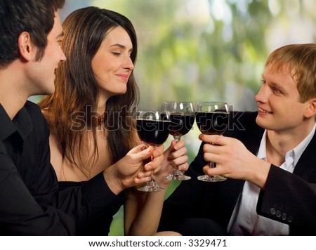 Two young happy smiling men flirting with attractive woman with red-wine, at celebration or party - stock photo