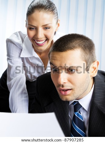 Two young happy smiling successful businesspeople working with document or contract at office