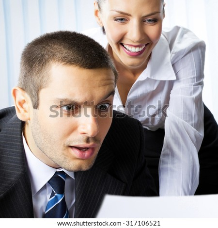 Two young happy smiling surprised businesspeople working with document or contract at office - stock photo