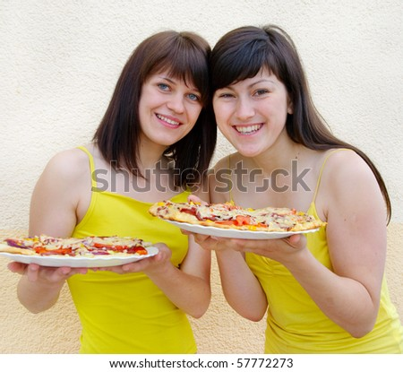 Two young happy woman with pizza