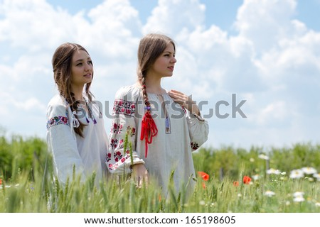 Two young happy women in traditional Ukrainian dress in wheat field on summer outdoors background - stock photo