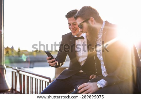 Two young hipster designers looking offer at their smartphone. Shallow depth of field, lens flare - stock photo
