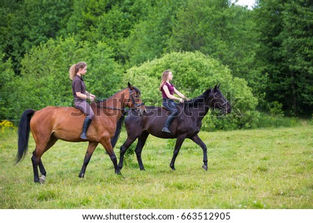 Two young horse riders in the woods in summer