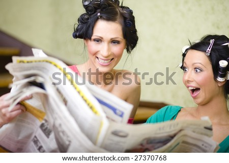 Two young housewives reading newspaper and looking for some cheap things - stock photo