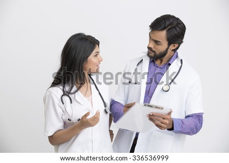 Two young Indian attractive doctors examining the document.
