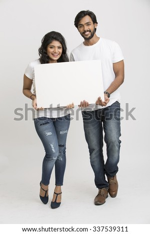 Two young Indian people holding a blank billboard white background - stock photo