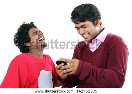 Two young  Indian students reading messages on their  mobile and  laughing out loud. - stock photo