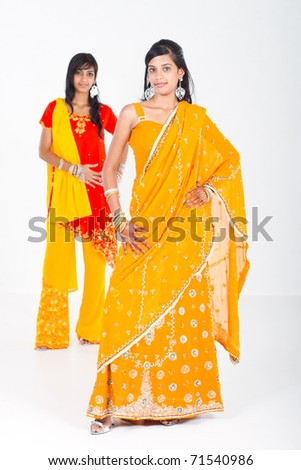two young indian women in traditional sari in studio - stock photo