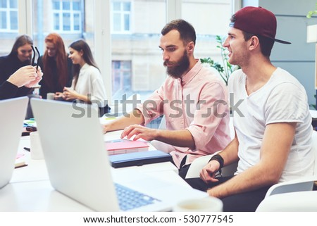 Two young IT professionals coding program for outsourcing creating apps for digital devices while sitting in coworking office using laptop computer and fast 4g wireless connection to internet