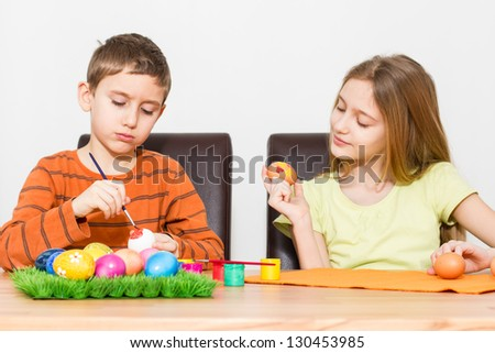 Two young kids painting Easter eggs