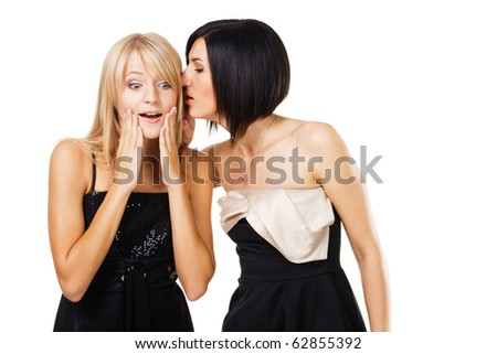 Two young ladies are gossiping - stock photo