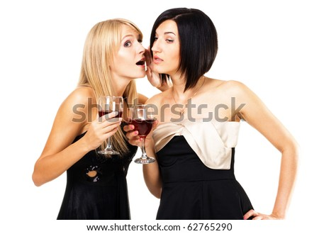 Two young ladies on the party are gossiping - stock photo