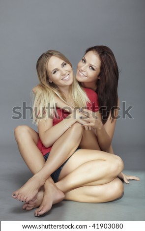 Two young ladies sitting on the floor and embracing each other - stock photo