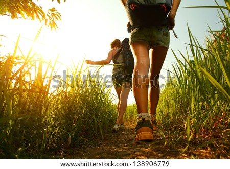 Two young ladies walking with backpacks through green lush meadow - stock photo