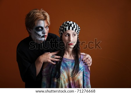 Two young ladies wearing makeup for All Souls Day - stock photo