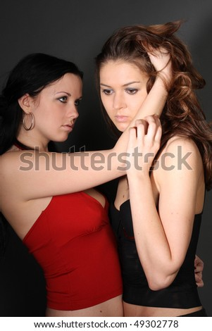 two young lesbian girlfriends on gray background