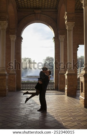 Two young lovers enjoying each other.  Square in Sevilla, Spain.  - stock photo