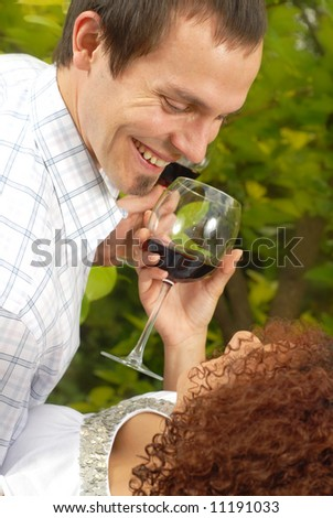 Two young lovers having some wine and sharing laughs at the park - stock photo