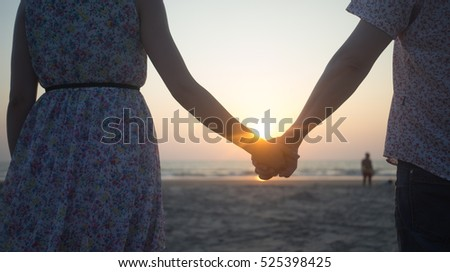 Two young lovers holding hands and go into sunset on the Arambol beach