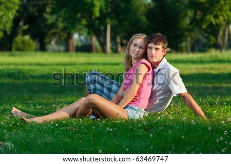 Two young lovers sitting on the lawn in the park and looks into the camera - stock photo